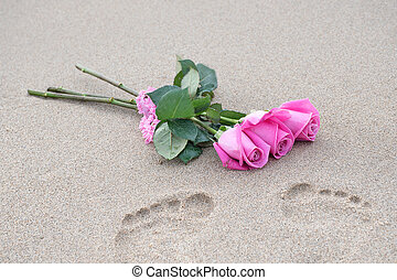 pink rose bouquet with footprint in sand
