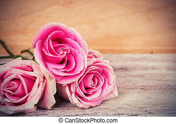 pink rose flower on wooden background