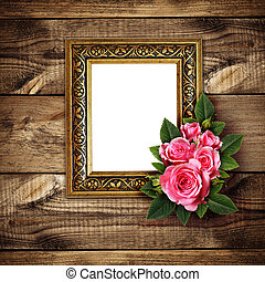 Pink rose flowers arrangement and a frame on wood