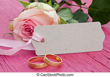 Pink rose with gift tag and petals