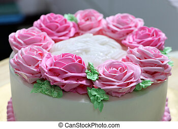 Pink roses and green leaf of butter cream on the white cake.