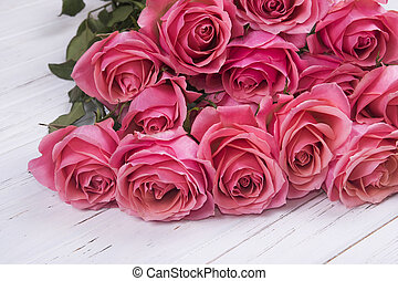 Pink roses bouquet on white wooden background.