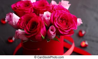 Pink roses bouquet packed in red box and placed on black...