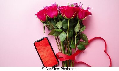 Pink roses bouquet with hart shaped bow and mobile phone...