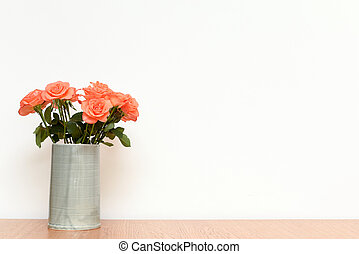 Pink Roses flowers in a vase on wooden table with white interior wall background