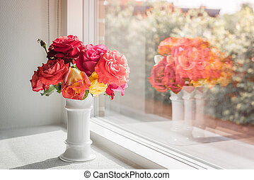 Pink roses in a window - Vase with pink and red roses in a...