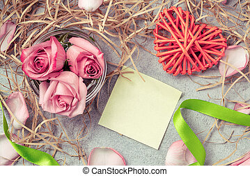 Pink roses in the water, a wicker heart, ornaments and an empty form for a note on the table