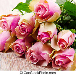 Pink roses isolated on wood background