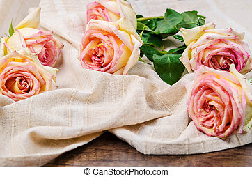 Pink roses on tablecloth.