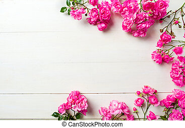 Pink roses on wooden background top view