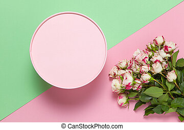 Pink round gift box, bouquet of small roses on pastel two-color background pink and green, copy space, flat lay. March 8, February 14, St. Valentine's, Mother's, Women's day celebration concept