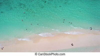 Pink sand and turquoise water beach top down view. People relax, swim, snorkel, sunbathe on perfect tropical shore. Nature background. Exotic summer vacation. Travel, outdoor tourism. Drone flight
