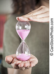 pink sand clock in woman hands over green background