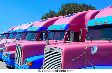 A fleet of semi trucks in an unlikely pink colour, parked outside of a circus in Fulton, Texas.