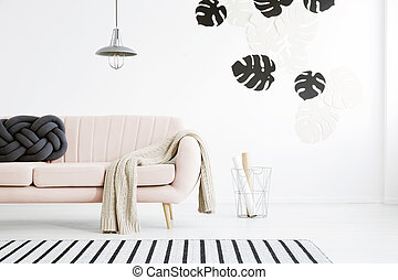 Pink settee in living room - Knot pillow and knit blanket on...