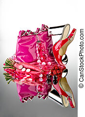 Pink shoes and purse with accessories and vegetable on a ...