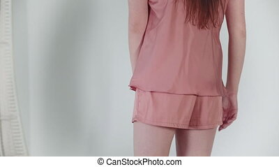 Pink shorts closeup. Happy girl dancing in front of the camera, posing in new pajamas on a white background.