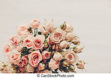 Pink small roses bouquet on white background isolated. Top view with space for text. Floral greeting card mockup. Wedding invitation, happy mother or Valentine day. Vintage tone