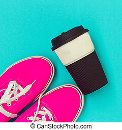 Pink sneakers and a cup on blue background