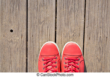 Pink sneakers on the wooden boards