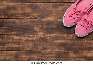 Pink sneakers on wooden background.