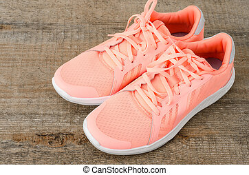Pink sneakers on wooden background