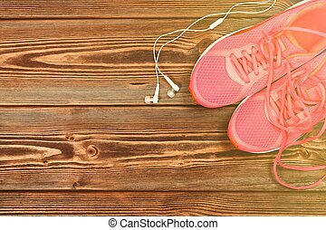 Pink sneakers on wooden texture