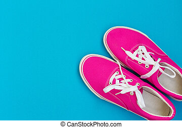 Pink sneakers with white laces on a blue