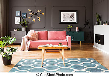 Pink sofa in grey living room interior with poster above green cabinet with plant. Real photo