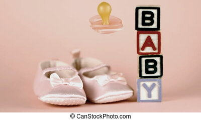 Pink soother falling in front of baby shoes and blocks...