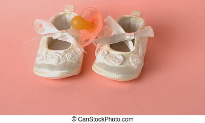 Pink soother falling onto baby shoe