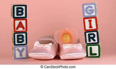 Pink soother falling onto baby shoes besides baby blocks in...