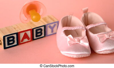 Baby pacifier falling onto booties in front of wooden letters in slow motion