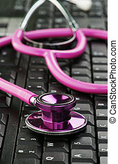 pink stethoscope on keyboard