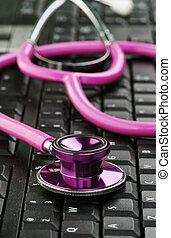 pink stethoscope on keyboard
