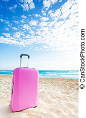 Pink suitcase on the beach