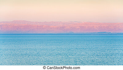 early pink sunrise and view of Jerusalem in sunbeam on Dead Sea coast