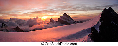 pink sunrise over glacier and high mountain peaks in the Alps