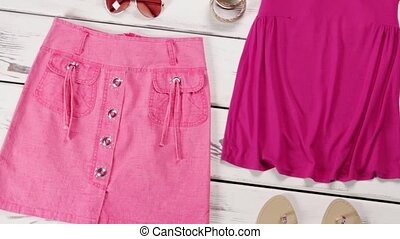 Pink tank top and skirt. Pink garments on white floor. Bright outfit for teenage girls. Skirt with top on sale.