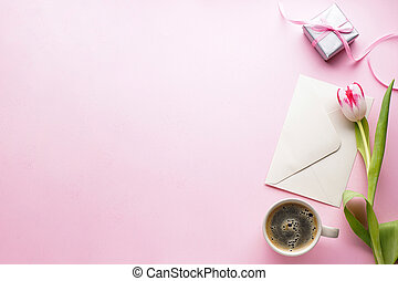 Pink tulip with a gift box and a letter on a pink background with space for text, flat lay. Greeting card template. 8 March, International Women's Day.