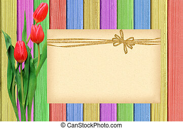 Pink tulips and card over shabby paint wooden table