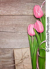 Pink tulips and gift box on wooden background