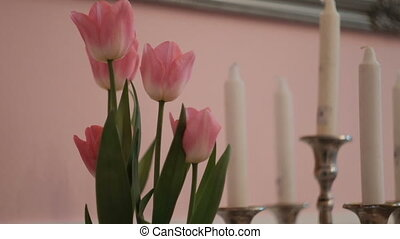 Pink tulips and white candles on table in living room....