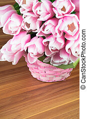 Pink tulips in a basket on wood