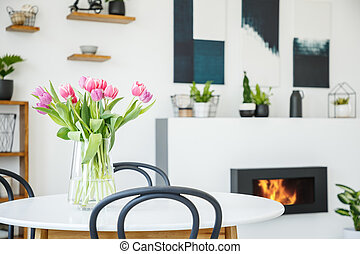 Pink tulips on dining table in white room interior with...