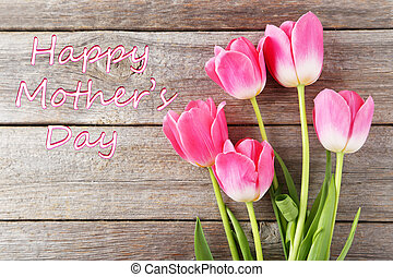 Pink tulips on grey wooden background