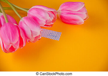 Pink tulips on the yellow background with note love love letter . Copy space.