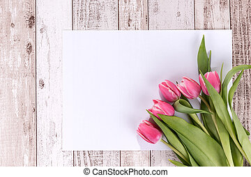 Pink tulips on wooden background with a white card