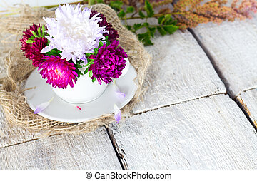 Pink vintage flower on white wooden background.
