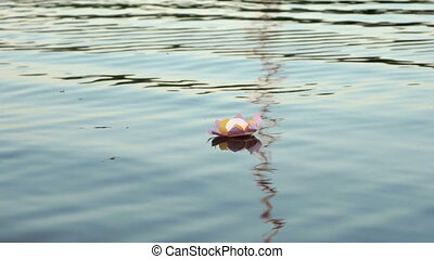 Pink water lily with candle on the water - Festive ritual -...